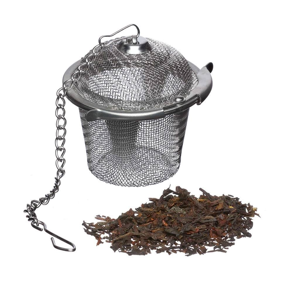 stainless steel tea basket on a chain with some tea leaves in front