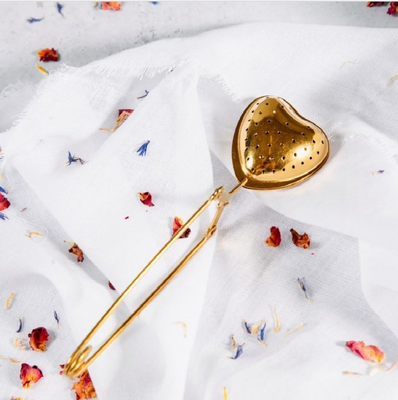 an image of a brass heart shaped tea infuser with a handle that you squeeze to open lying on some white cloth with herbal tea sprinkled around it